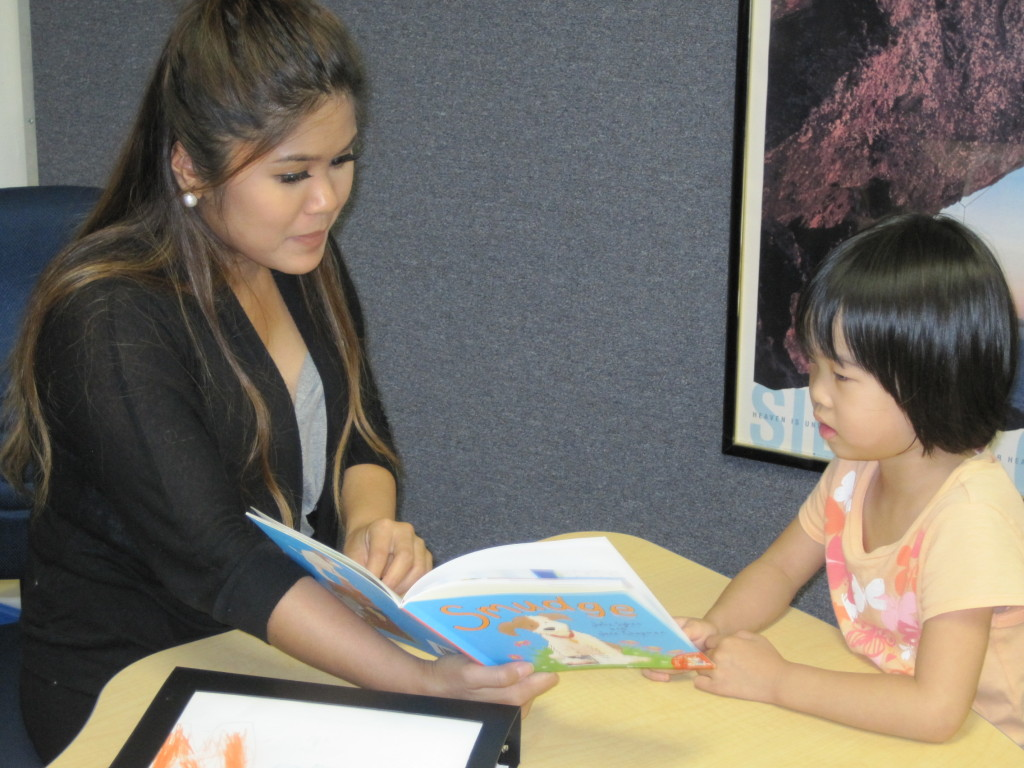 Teacher Katherine reading to a young student.